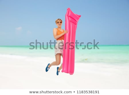 teenage girl jumping with float mattress on beach Stock photo © dolgachov