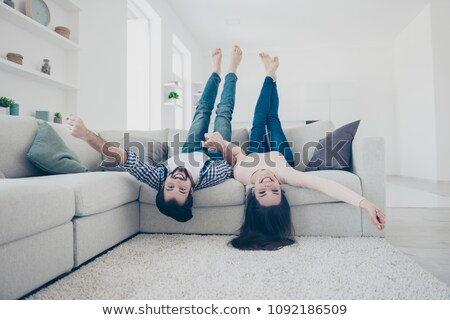 Young couple laying on the sofa with heads upside down Stock photo © Lopolo