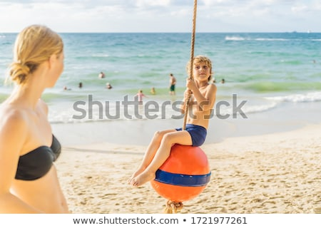 A boy on a swing on the beach. Mom and son spend time on the beach BANNER, LONG FORMAT Stock photo © galitskaya