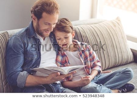 Syn ojca czytania książki sofa domu rodziny Zdjęcia stock © dolgachov