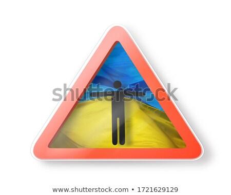 Warning sign with man's figure on the Ukrainian flag. Stock photo © artjazz