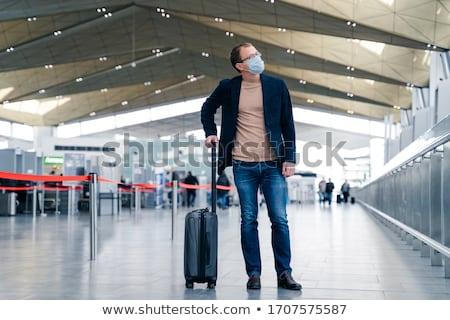 Horizontal full length shot of European man in medical mask looks away, returns from trip, stands wi Stock photo © vkstudio