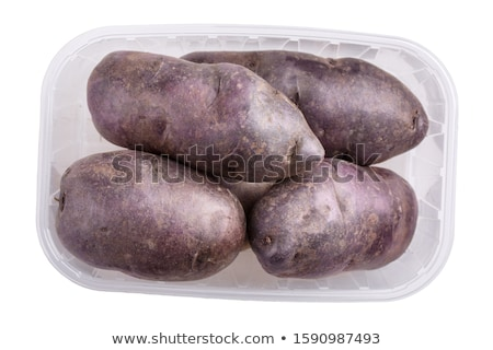 Raw potatoes in red tray and potato peels, isolated Stock photo © elly_l