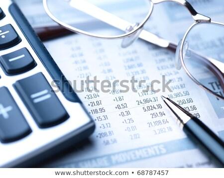 glasses and calculator on a newspaper stock photo © jakatics