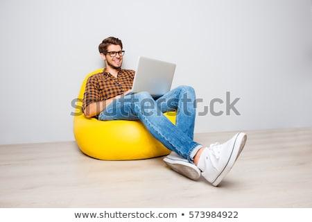 Jonge man vergadering vloer geïsoleerd witte gezicht Stockfoto © ashumskiy