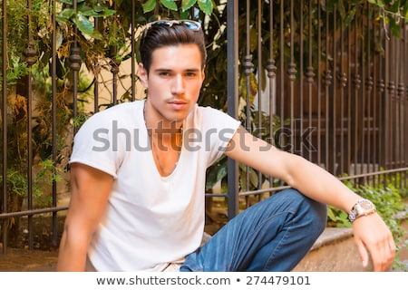 serious cool casual man wearing sunglasses and sits stock photo © feedough