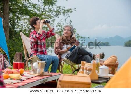 Senior man with binoculars in front lake Stock photo © IS2