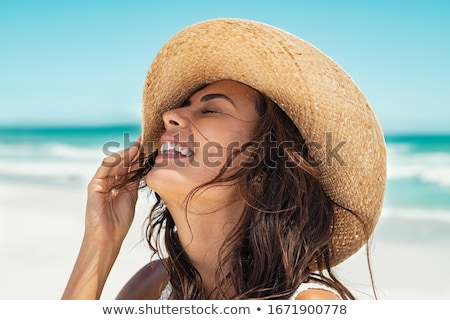 Girl holding out straw hat on beach Stock photo © IS2