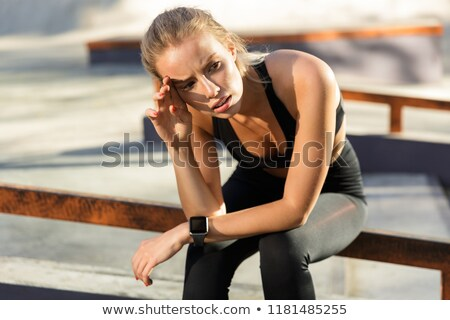 Tired bored oung sports woman sitting outdoors looking aside. Stock photo © deandrobot