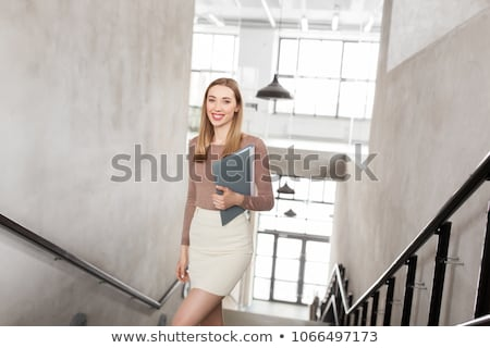happy woman with folder walking upstairs Stock photo © dolgachov