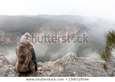 Female sitting on the cliff ledge looking out into the misty fog Stock photo © lovleah