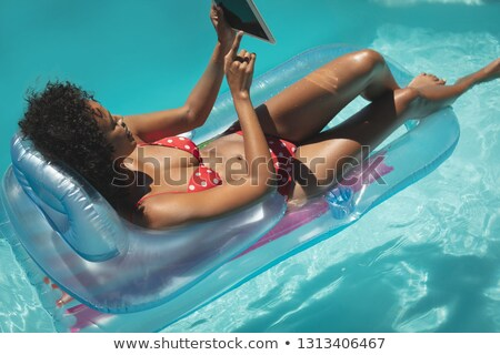 High angle view of young African American woman relaxing on pool lounger and using digital tablet in Stock photo © wavebreak_media
