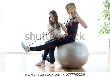 Woman with physical therapist doing exercises on fitness ball Stock photo © Kzenon