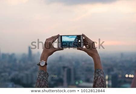 Nő fotó naplemente mobiltelefon ül nyár Stock fotó © dashapetrenko