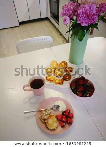 Fresh pastries and a cup of coffee for tomorrow on the table decorated with flowers Stock photo © ElenaBatkova