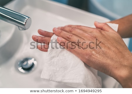Washing hands steps for personal hygiene COVID-19 prevention drying hand with paper towel after hand Stock photo © Maridav