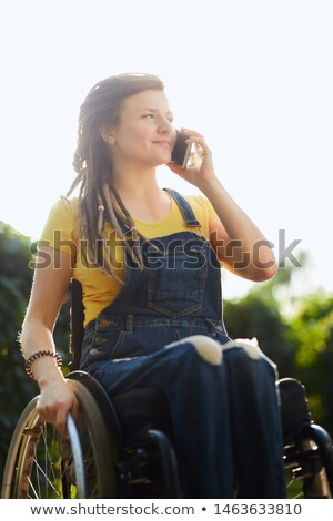 Girl with dreadlocks and piercing talking by mobile phone. Stock photo © deandrobot