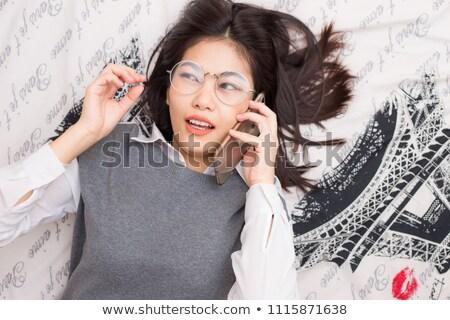 beautiful happy blond woman talking on cell phone lying down on stock photo © dacasdo