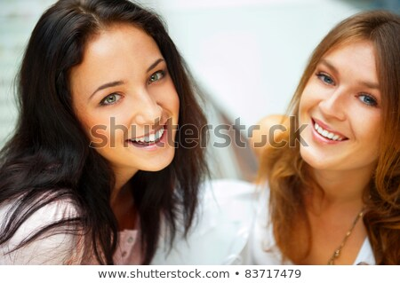 Two women whispering and smiling while shopping inside mall stock photo © HASLOO
