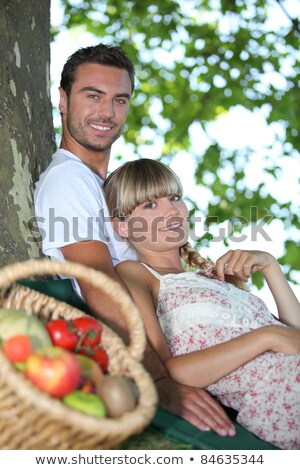 Couple sat by tree with basket of fresh produce Stock photo © photography33