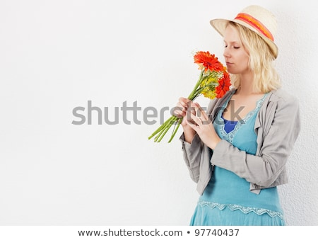 Woman smelling at a flower with eyes closed against white background Stock photo © wavebreak_media