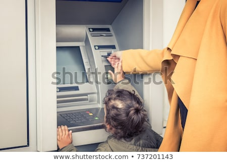 Woman inserting her bank card into an ATM Stock photo © stryjek