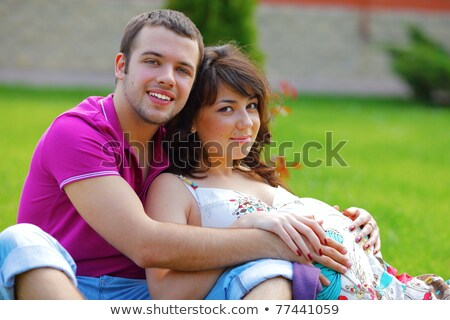 happy beautiful pregnant woman with his husband sitting on the lawn outside stock photo © deandrobot