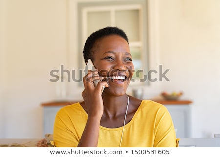 portrait of a happy woman talking on the phone at home stock photo © deandrobot