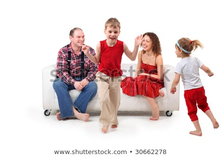 Parents sit on white leather sofa and look at running children stock photo © Paha_L