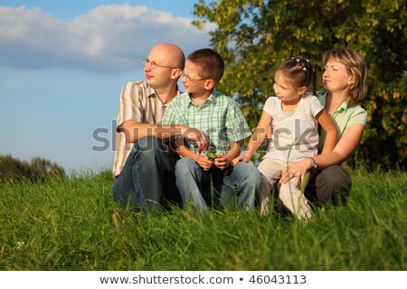 Stock photo: Dad, mom, son and daughter in early fall park. they sitting on grass and looking at sunset
