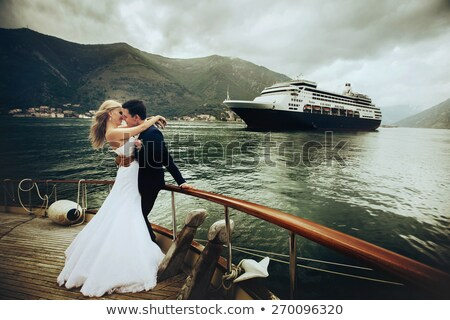 Young beautiful married couple kissing on the yacht Stock photo © deandrobot