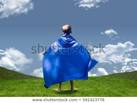 Boy in superhero costume standing on grasslands against sky in background Stock photo © wavebreak_media