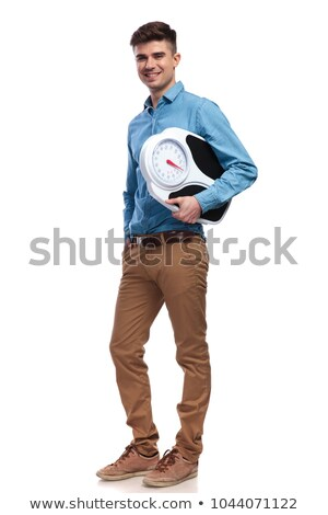 full body picture of a smiling man holding a scale Stock photo © feedough