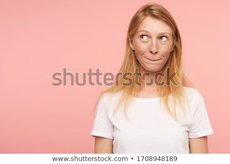 young lady standing over pink biting lip stock photo © deandrobot