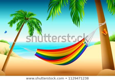 rainbow striped hammock on beach between palm trees summer holiday vacation stock photo © orensila