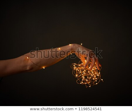 womans hand decorate with yellow garlands around a black background with copy space christmas stock photo © artjazz