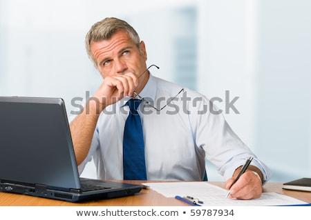 Nachdenklich reifen Geschäftsmann nachschlagen Konzentration schriftlich Stock foto © Minervastock