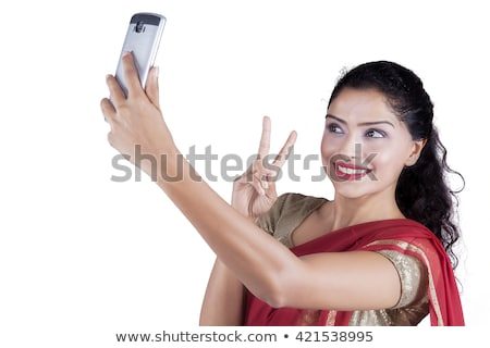 Happy young asian beautiful attractive woman posing isolated indoors take selfie by mobile phone. Stock photo © deandrobot
