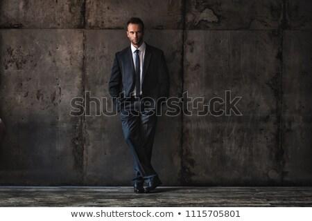 handsome man wearing black suit on a grunge background. stock photo © doodko