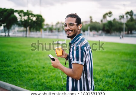 Cheerful young guy listening music with earphones in the park chatting by phone. Stock photo © deandrobot