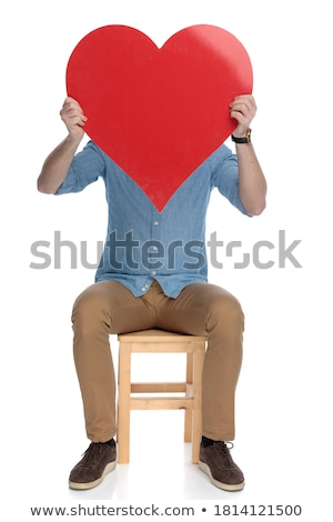 seated modern man holding a big red heart over face stock photo © feedough