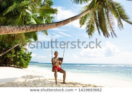 man sitting on swing looking at digital tablet at beach stock photo © andreypopov