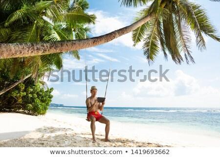 Hombre sesión swing mirando digital tableta Foto stock © AndreyPopov