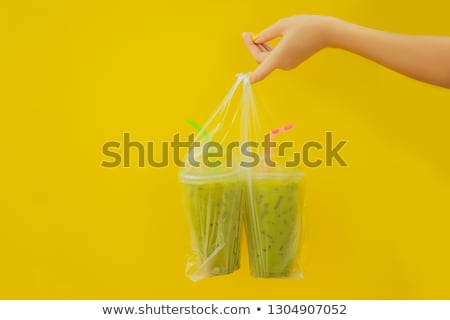 two green tea latte with ice in plastic cup and straw in female hand with yellow manicure on yellow stock photo © galitskaya