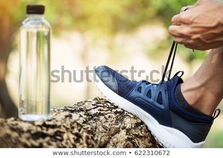 Shot of young woman runner tightening running shoe laces, gettin Stock photo © Freedomz