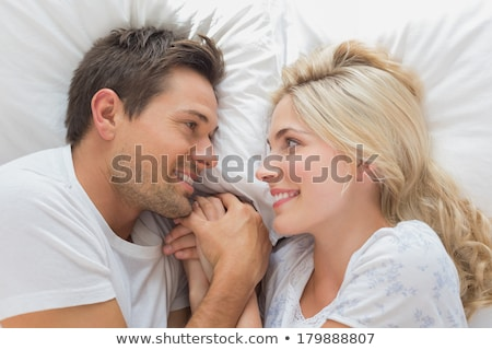 couple holding each other hand while lying on bed stock photo © andreypopov
