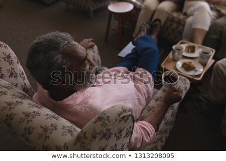 High angle view of senior man having black coffee in living room and sitting on sofa  at home Stock photo © wavebreak_media