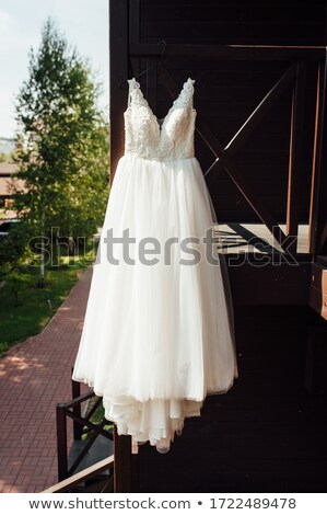 Elegant wedding dress hanging on a wooden railing outside Stock photo © ruslanshramko