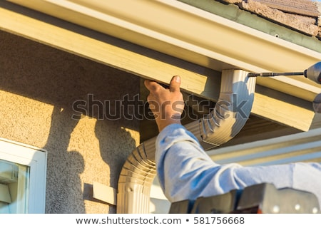 Workers Attaching Aluminum Rain Gutter to Fascia of House Stock photo © feverpitch