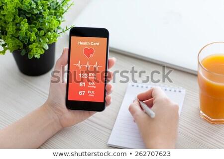 Doctor showing app for measuring of heart pulse. Stock photo © RAStudio